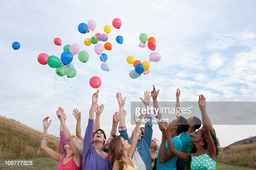Young people releasing balloons : Stock Photo