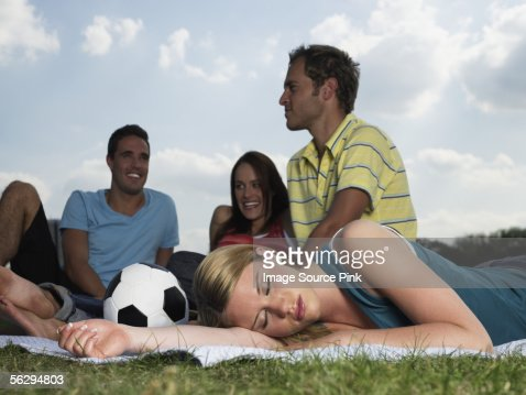 Young people resting in a field : Stock Photo