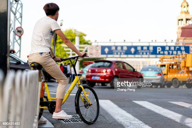 Young people ride the Ofo bikes on city street In the first quarter of 2017 Ofo has developed 451 million new users covering 100 cities in the world...