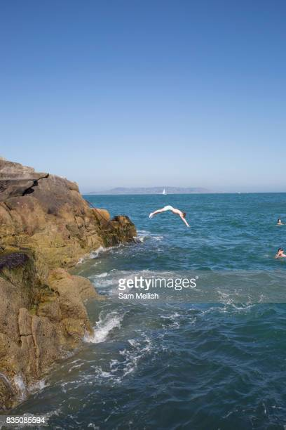 Young people rock diving into Dublin Bay at Sandycove on 08th April 2017 in County Dublin Republic of Ireland Sandycove is a popular seaside resort...