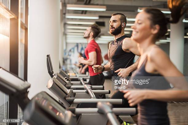 Young people running on treadmills in health club.