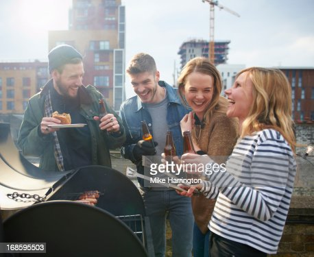 Young people sharing beers around barbecue. : Photo