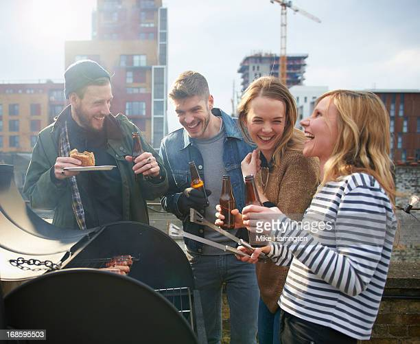 Young people sharing beers around barbecue.