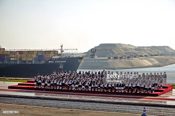 Young people sing during the official opening ceremony as a the container ship MSC Chicago passes through a section of the New Suez Canal operated by...
