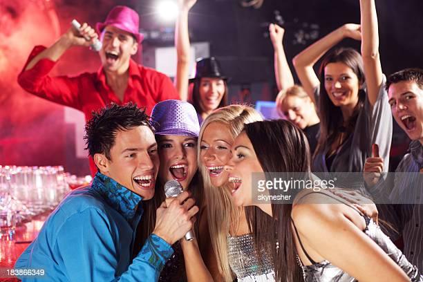 Junge Menschen singen mit Mikrofon in Ihren Händen.