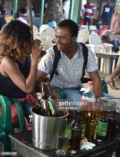 Young people sit at a table with beer bottles at a bar in Abidjan on July 13 2017 On posters and huge billboards around the country rival ads by two...
