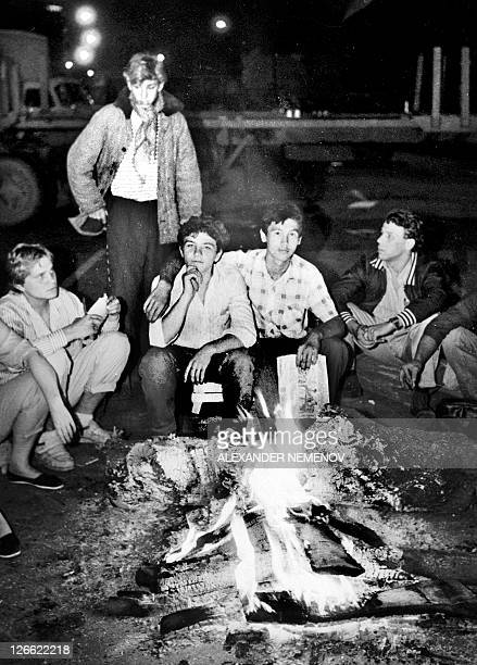Young people sit in front of a fire next to the Russian White House in central Moscow early on August 20 1991 Russia marks on August 1922 the 20th...