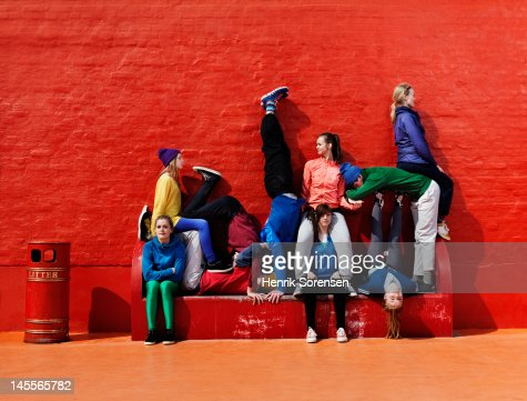 Young people sitting and stading on a bench