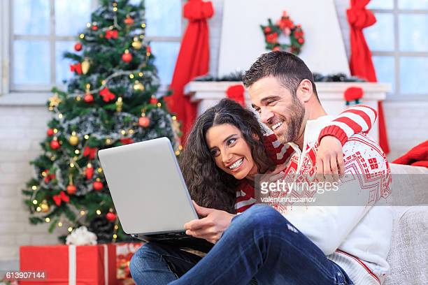 Young people sitting on couch and using laptop at home