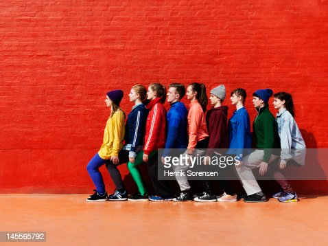 Young people sitting on each other in a line. : Stock Photo