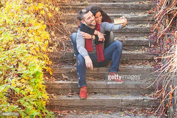 Young people sitting on stairs and making selfie