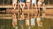Legs of young people sitting on the edge of a jetty hanging down to the water. Group of friends hanging out at the lake.