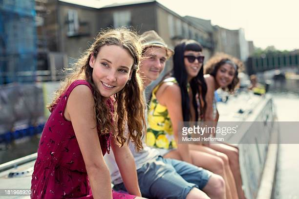 Young people sitting on top of canal boat
