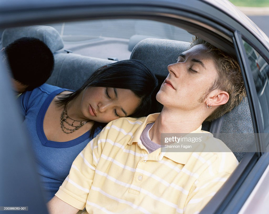 Young people sleeping in backseat of car : Stock Photo