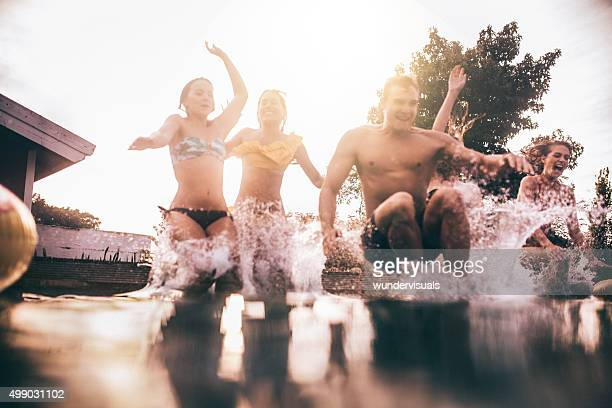 Young people splashing into a pool having jumped in together