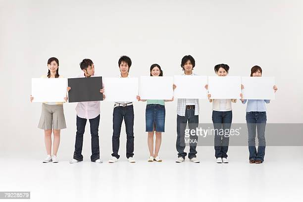Young people standing with blank message board