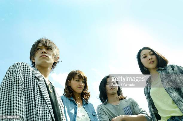 Young people standing with sky background