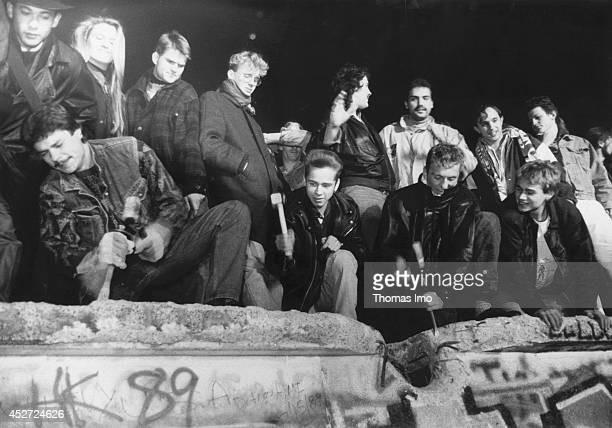 Young people start tearing down the Berlin Wall after opening of the border on November 09 in Berlin Germany The year 2014 marks the 25th anniversary...