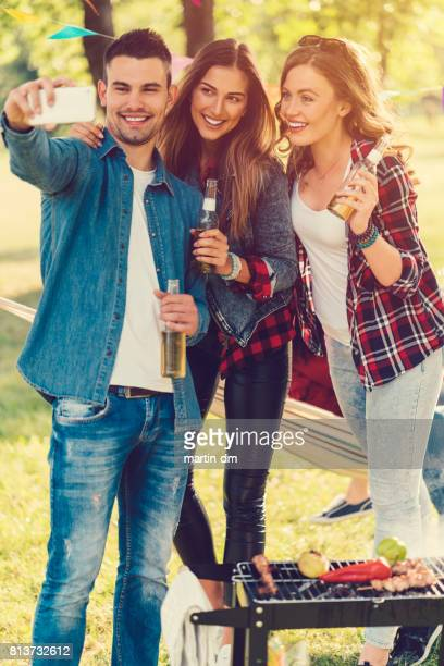 Young people taking selfie at barbeque party