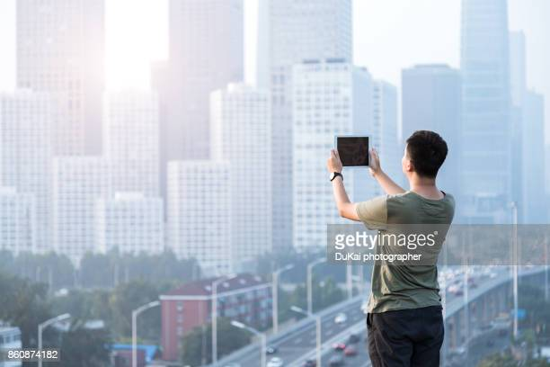 Young people use tablet computers on the roof