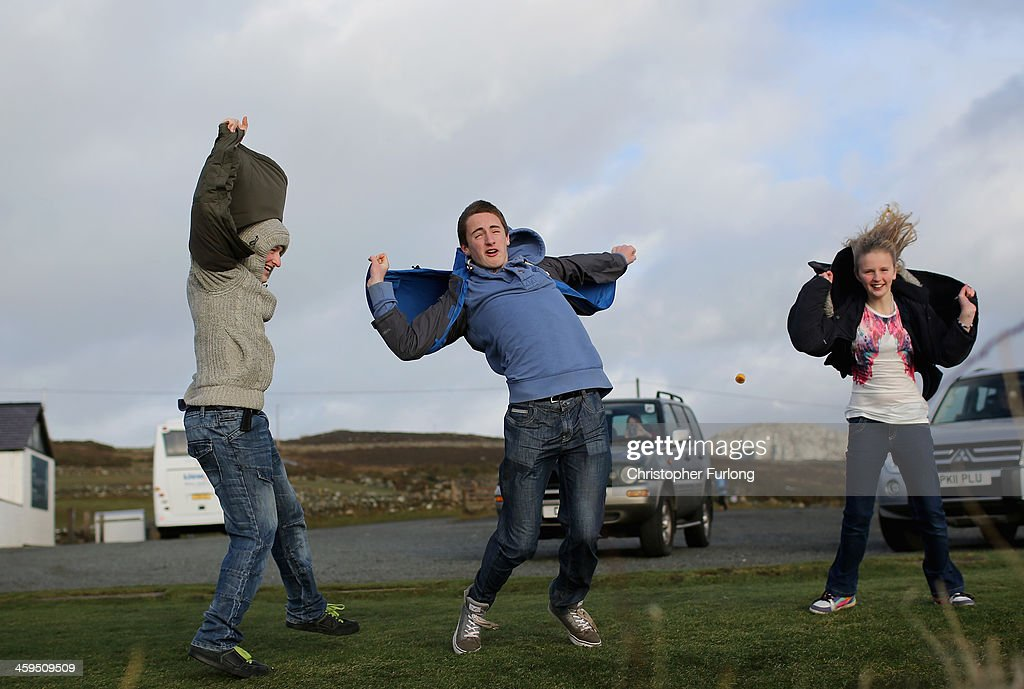 Young people use their coats as sails as they brave the gale force winds near South Stack lighthouse on December 27, 2013 in Anglesey, United Kingdom. A yellow 'be aware' warning has been issued for many parts of Britain as the country is affected by gale force winds and heavy rain.
