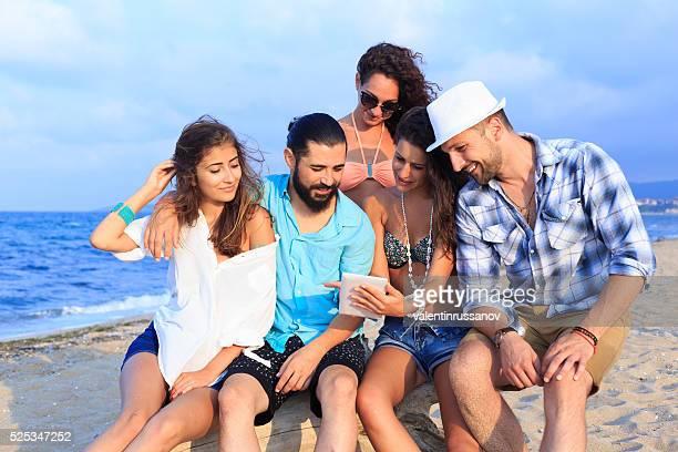 Jeunes à l'aide de tablette numérique sur la plage