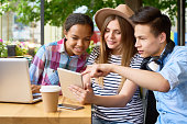 Multi-ethnic group of happy students studying using laptop and digital tablet in outdoor cafe on sunny summer day