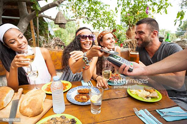 Young people using smart phone for contactless payment in restaurant