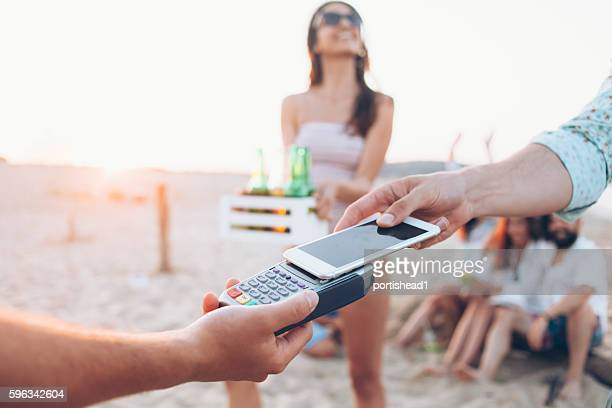 Young people using smart phone for paying on beach