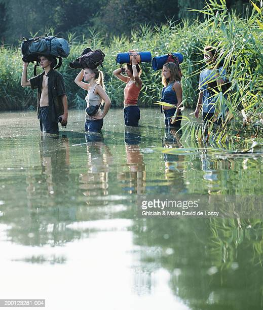 Young people wading through river, bags resting on heads, side view