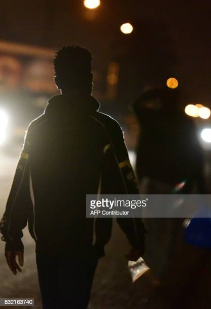 Young people walk in the neighbourhood of Abobo a suburb of Abidjan on August 3 2017 'Microbe' is a term used by Ivorians for children and young...