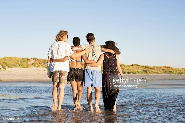 Young people walking in water at beach