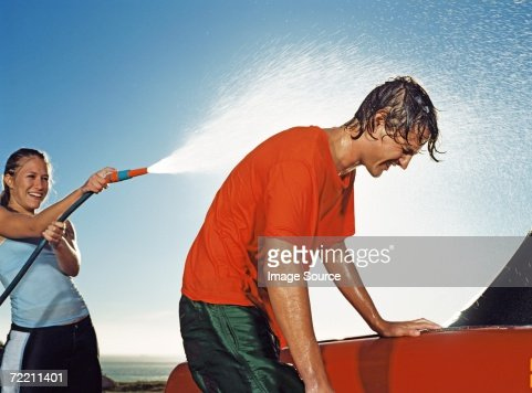 Young people washing car and having water fight