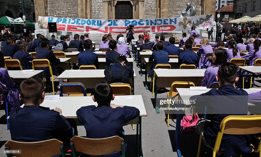 Young people, wearing white ribbons on their arms, sit at the desks in front of the Cathedral of Jesus' Heart to commemorate non-Serb civilians killed in the war on the territory of western town of Prijedor, in Sarajevo, Bosnia and Herzegovina on May 31, 2016. Names and ages of children, killed in Prijedor is written on the desks.