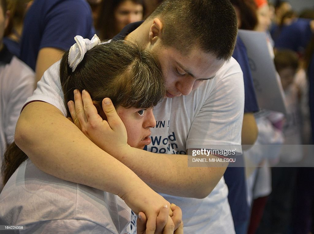 Young people with Down Syndrome embrace each other during an event marking the International Day of Down Syndrome in Bucharest March 21, 2013. March 21 aims to raise awareness among the population regarding people with Down syndrome and combat some wrong social perceptions, depriving these people of their right to an active life.