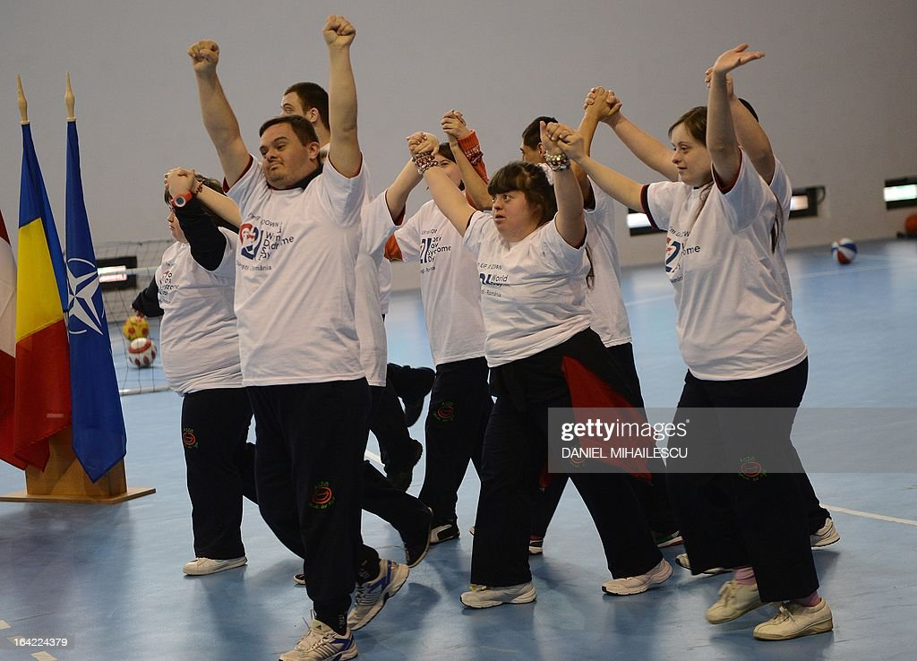 Young people with Down Syndrome salute the audience during an event marking the International Day of Down Syndrome in Bucharest March 21, 2013. March 21 aims to raise awareness among the population regarding people with Down syndrome and combat some wrong social perceptions, depriving these people of their right to an active life.