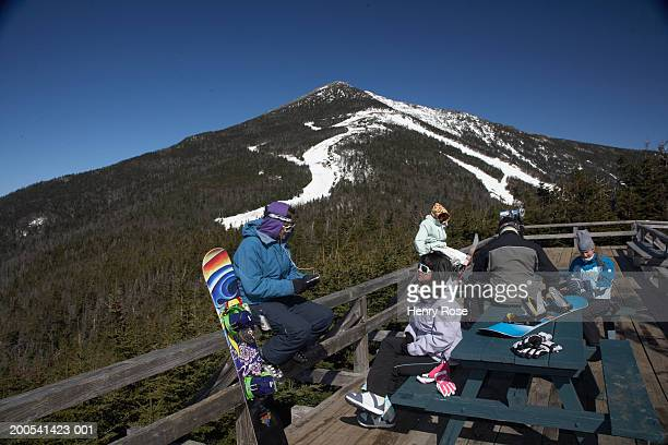 Young people with snowboards on scenic lookout