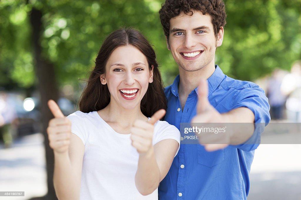 Jovens com polegares para cima : Foto de stock