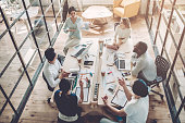 Top view of multiracial young creative people in modern office. Group of young business people are working together with laptop, tablet, smart phone, notebook. Successful hipster team in coworking. Fr