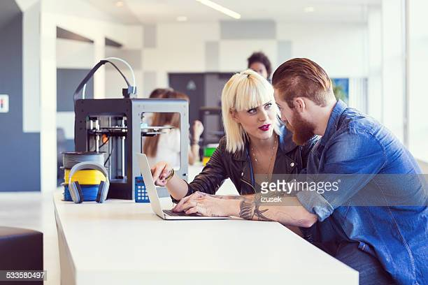 Young people working on laptop in 3D printer office