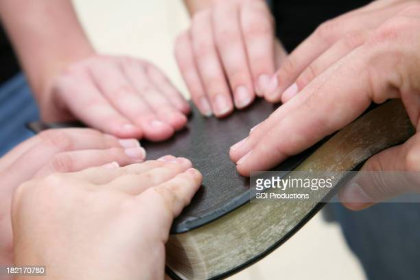 Young People's Hands on a Black Bible