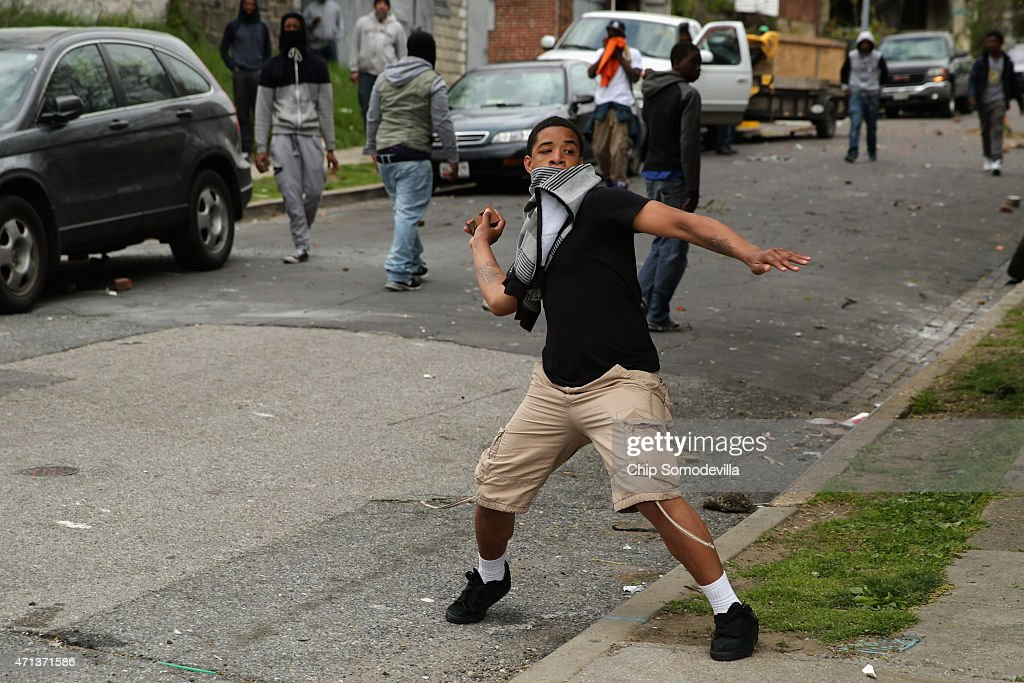 Young person hurls a rock at Baltimore Police officers outside the Mondawmin Mall following the funeral of Freddie Gray April 27 2015 in Baltimore...