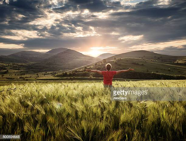 Jungen Sitzen im Freien im weath field Positive Emotionen