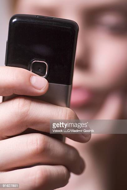 A young person taking a picture with a cellular phone
