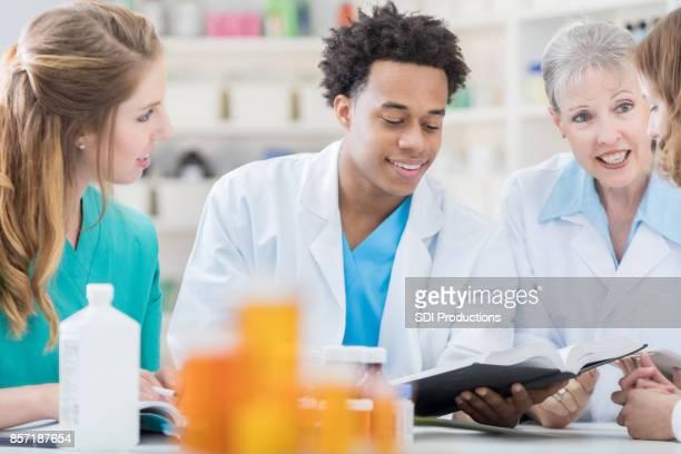 Jonge apotheker leest als hij naar collega's tijdens een vergadering luistert