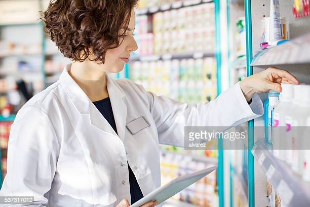 Young pharmacist with a tablet in drug store