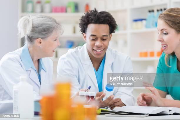 Jonge farmaceutisch technicus luistert naar collega's tijdens vergadering