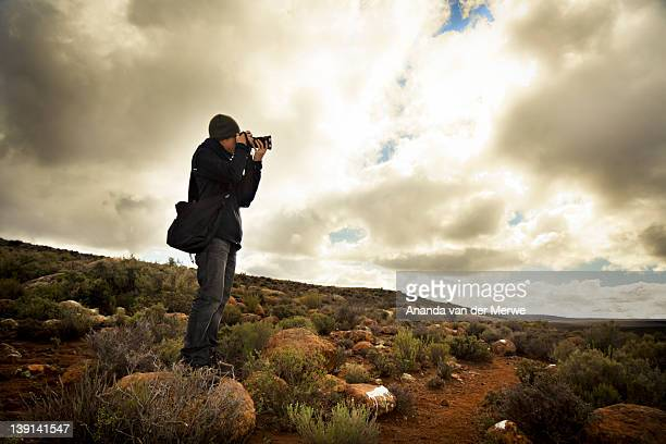 Young photographer aiming his camera to take a shot with beautiful nature scenery and dramatic sky in the background, Sutherland, Great Karoo, Groot Karoo, Northern Cape Province, South Africa
