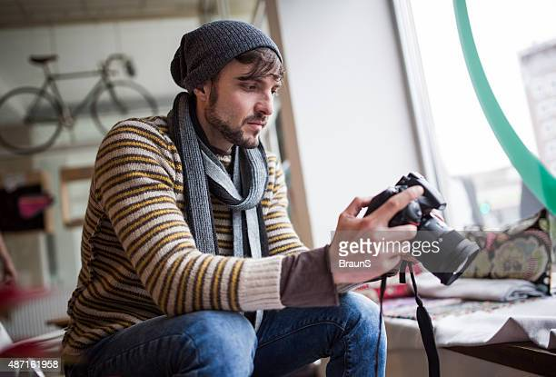 Young photographer looking at photos on digital camera.