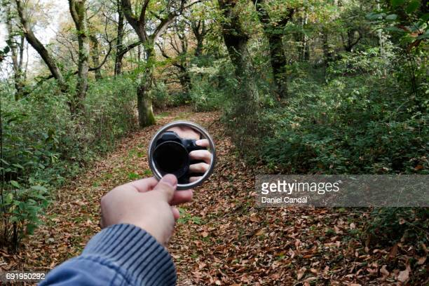 Young photographer reflected in mirror in luxuriant forest in Galicia (Spain)
